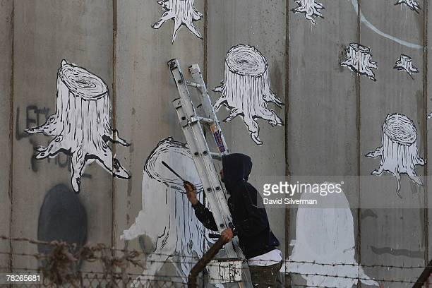 The Italian street artist Blu paints graffiti on Israel's separation barrier December 5 2007 where is cuts a path into the biblical West Bank city of...