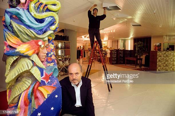 The Italian stylist Elio Fiorucci beside a work of art inside a hall The '90s