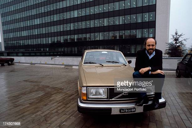 The Italian stylist Elio Fiorucci is seated on the bonnet of his car a Volvo 244 Gle 1981