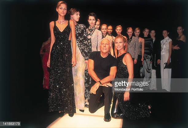 The Italian stylist Giorgio Armani kneeling on the catwalk at the end of a fashion show. Among the models there is also the Argentinian Valeria...