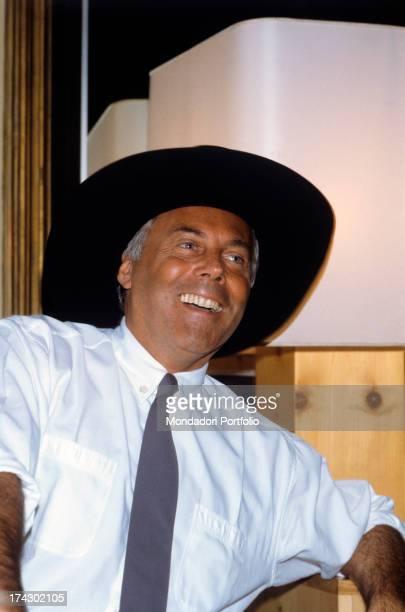 The Italian stylist Giorgio Armani smiles, wearing a flamboyant black hat..