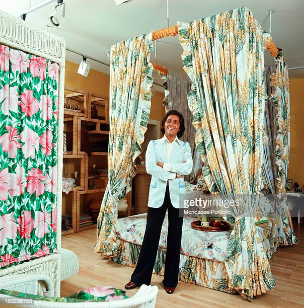The Italian stylist Valentino standing in his atelier in front of a fourposter bed designed by him in the 'Old America' style Rome 1972