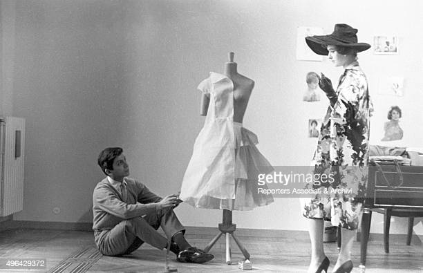 The Italian tailor Valentino dressing a mannequin in his first atelier A model wearing a flowered dress and a widebrim hat stands beside him Rome 1959