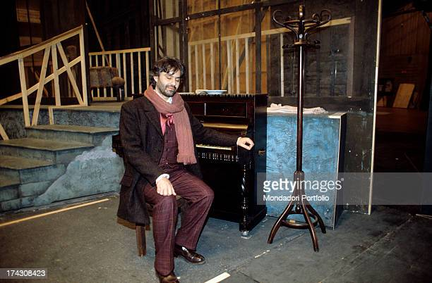 The Italian tenor Andrea Bocelli seated at a piano in the stage of Teatro Lirico of Cagliari with some elements of the scenography for La Boheme he's...