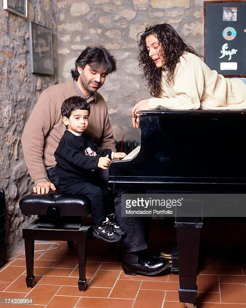The Italian tenor Andrea Bocelli seated at the piano alongside his two years old son Amos in their house in Tuscany while Bocelli's wife Enrica...