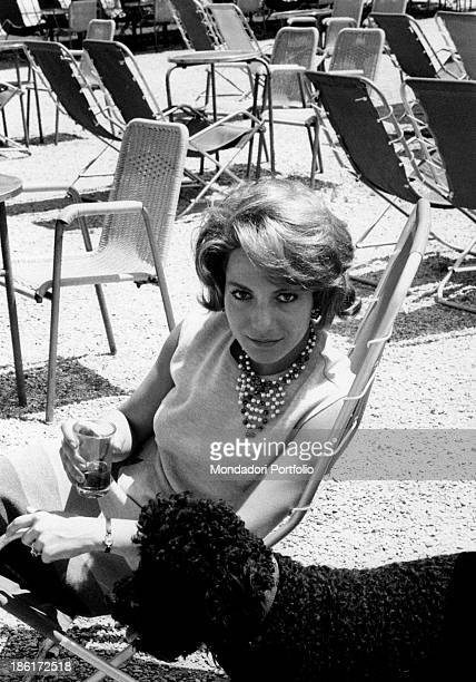 The Italian TV announcer Mariolina Cannuli is seated on a garden chair looking at the camera she is holding a glass in her hand Next to her her...