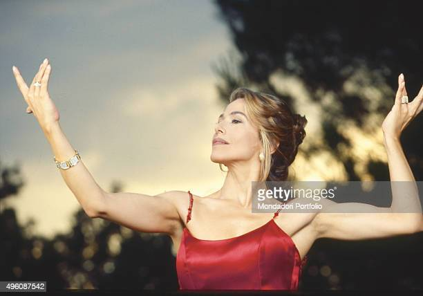 The Italian TV presenter and actress Barbara D'Urso posing in a red glittering dress during a photo shoot in a garden Italy 1998