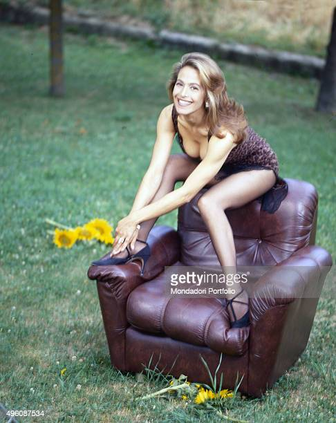 The Italian TV presenter and actress Barbara D'Urso sitting in an armchair during a photo shoot in a garden Italy 1998