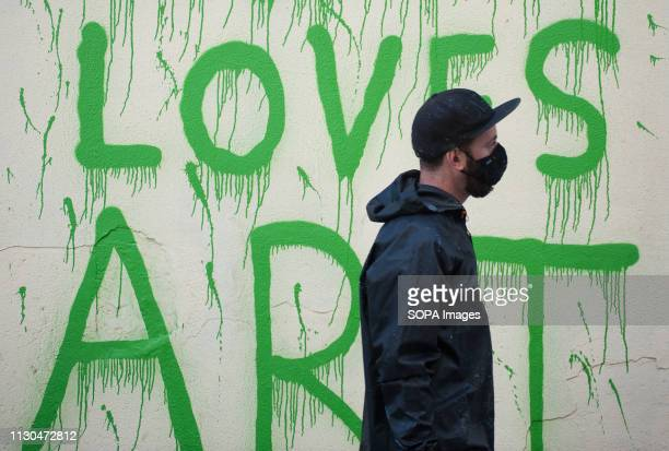 The Italian urban artist TVBOY is seen walking past a mural at the 'Soho' urban district in down town Malaga The participation of urban artist TVBOY...