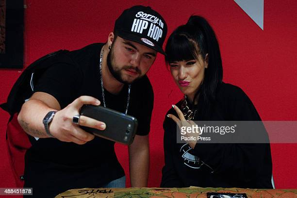 The Italian woman rapper Claudia Nahum also known as 'Baby K' poses with her fan during the autograph signing of her new album 'Kiss Kiss Bang Bang'...