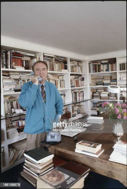 The Italian writer and director Alberto Bevilacqua standing in his office while talking on the phone Behind him a large library full of books Rome...