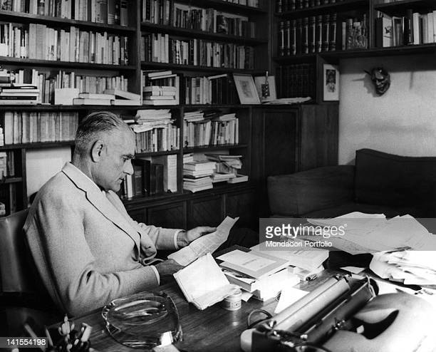 The Italian writer and journalist Alberto Moravia reading seated in his study 1960s