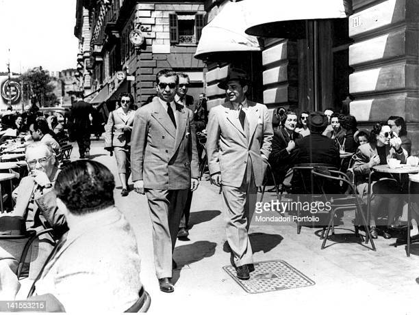 The ItalianAmerican gangster Lucky Luciano walking with his counsel George Wolf Italy 1950s
