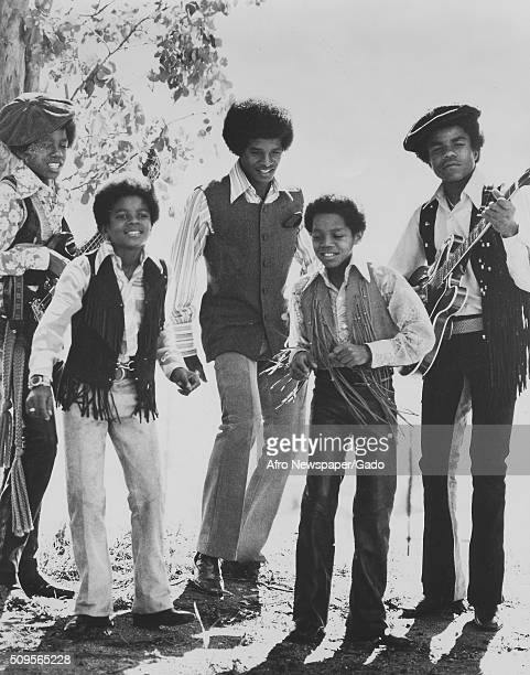The Jackson Five singing and playing guitars outdoors from left Tito Michael Toriano Jackie and Jermaine 1975