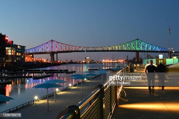 The Jacques-Cartier bridge in Montreal is seen on April 11 from the tourist district of the Old Port, illuminated in the colours of the rainbow as a...