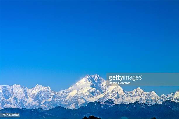 The jagged snow and ice summit of Mount Everest under a blue sky.