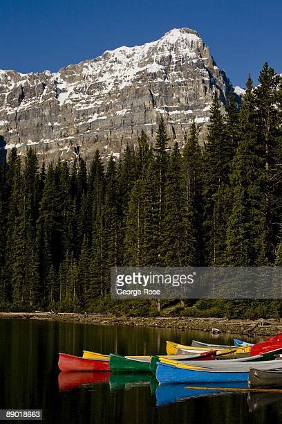 The jagged Valley of Ten peaks behind Moraine Lake are a backrop to brightly colored canoes in this 2009 Lake Louise, Canada, summer morning...