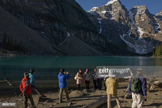 The jagged Valley of Ten Peaks lining Moraine Lake are a backrop to a group of Japanese tourists as seen in this 2009 Lake Louise, Canada, summer...