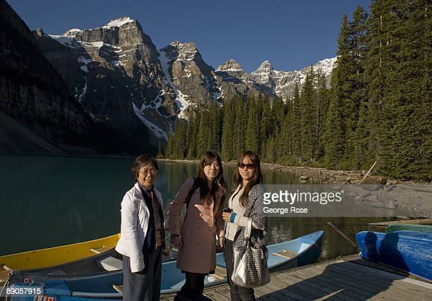 The jagged Valley of Ten Peaks lining Moraine Lake are a backrop to a group of Japanese tourists and several brightly colored canoes in this 2009...