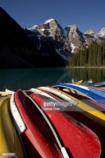 The jagged Valley of Ten Peaks lining Moraine Lake are a backrop to brightly colored canoes in this 2009 Lake Louise, Canada, summer morning...