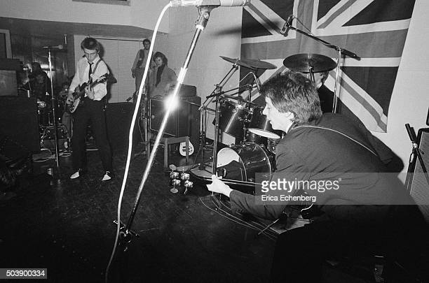 The Jam perform on stage at the Royal College of Art in front of a large Union Flag London 29th April 1977 LR Paul Weller Bruce Foxton
