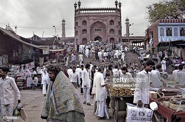 The Jama Masjid Mosque Gate 2 front view markets and a lunatic/insane man in 100 degree temperature with warm blankets Old Delhi INDIA