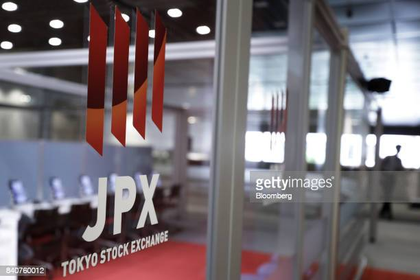 The Japan Exchange Group Inc logo is displayed on a glass door at the Tokyo Stock Exchange in Tokyo Japan on Wednesday Aug 30 2017 Equity indexes in...