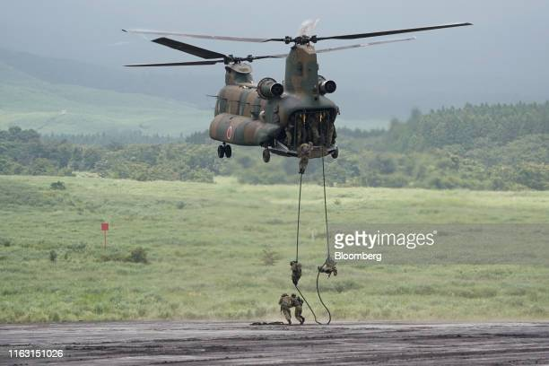 The Japan Ground Self-Defense Force soldiers rappel from a helicopter during a live fire exercise in the Hataoka district of the East Fuji Maneuver...