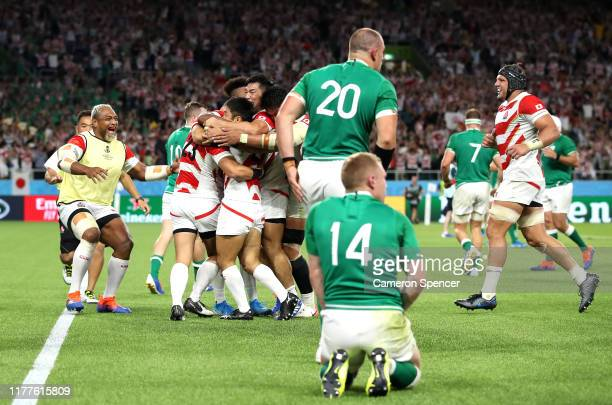 The Japan team celebrate victory as the Ireland players react to losing after the Rugby World Cup 2019 Group A game between Japan and Ireland at...