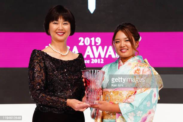 The Japanese LPGA Regular Tour Prize Money Queen Ai Suzuki is presented the trophy by the Japanese LPGA President Hiromi Kobayashi during the LPGA...