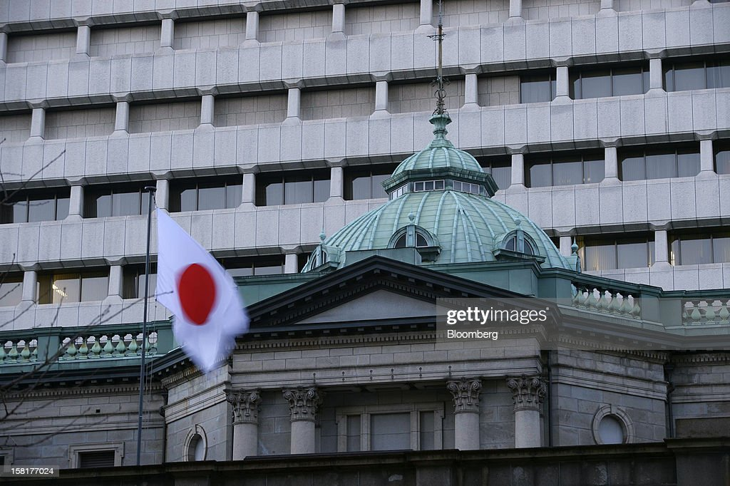 The Japanese national flag flies atop the Bank of Japan headquarters in Tokyo, Japan, on Monday, Dec. 10, 2012. Japan's bond market is signaling concern that a government run by Shinzo Abe will ramp up spending to revive growth, adding to a debt burden already twice the size of the nation's economy. Photographer: Akio Kon/Bloomberg via Getty Images
