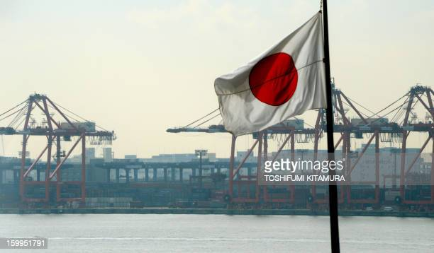 The Japanese national flag flies in front of the container pier in Tokyo port on January 24 2013 Japan said it logged a record trade deficit in 2012...