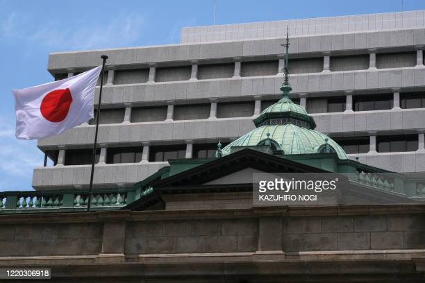 The Japanese national flag flies on a part of the Bank of Japan headquarters in Tokyo on June 16, 2020. - Japan's central bank on June 16 ramped up...