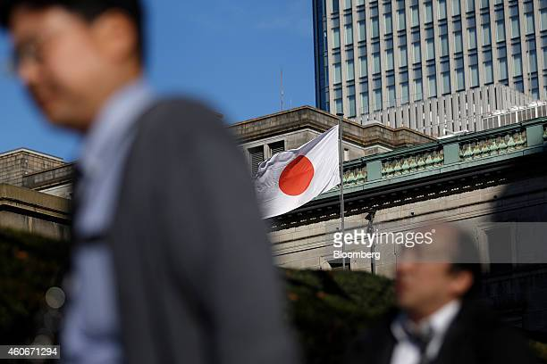 The Japanese national flag flies outside the Bank of Japan headquarters in Tokyo, Japan, on Friday, Dec. 19, 2014. The Bank of Japan maintained...