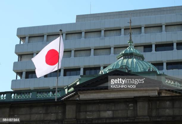 The Japanese national flag is seen on the Bank of Japan headquarters in Tokyo on July 29 2016 Tokyo shares rose on July 29 with lenders boosted by...