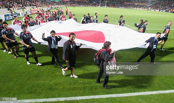 The Japanese squad parade a giant national flag around the ground following their team's late and dramatic 1212 draw during the Rugby World Cup Pool...