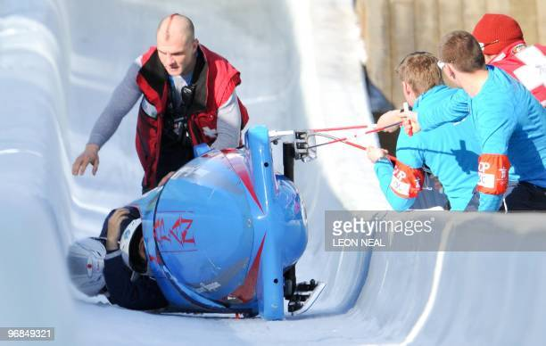 The Japanese twoman bobsleigh piloted by Hiroshi Suzuki is recovered by a rescue team on the ramp at the finish line after crashing during training...
