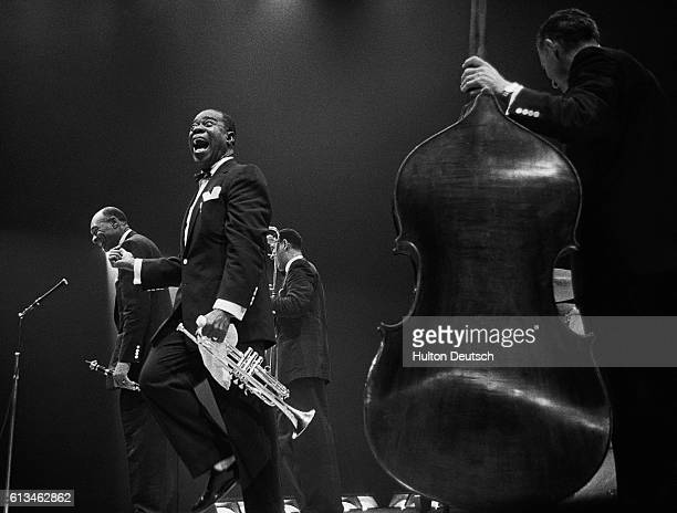 The jazz trumpeter and singer Louis Armstrong also known as Satchmo shouts with delight as his fellow performer Edmund Hall takes a bow after a solo...