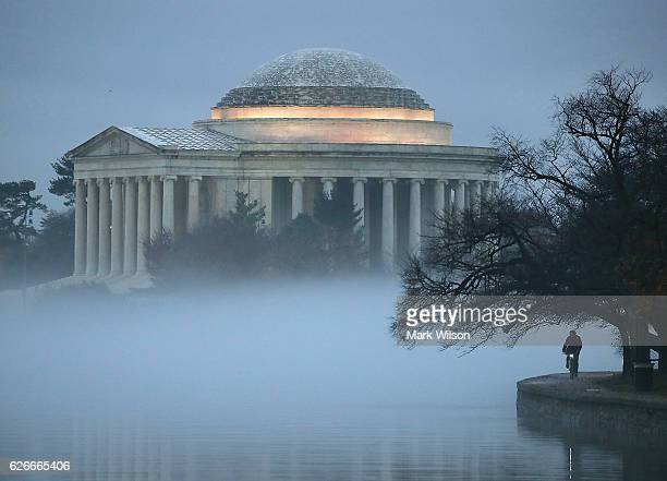The Jefferson Memorial is surrounded in fog as a man rides a bicycle along the Tidal Basin on November 30 2016 in Washington DC Today the Washington...