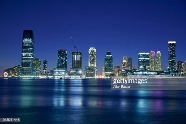 the jersey city waterfront with the '30 hudson street' tower at dusk - newark new jersey stock pictures, royalty-free photos & images