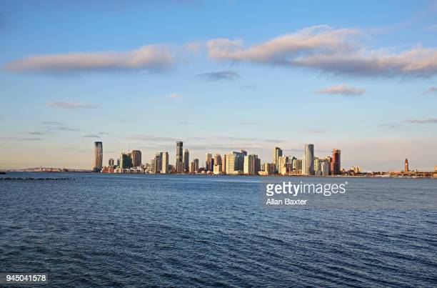 the jersey city waterfront with the '30 hudson street' tower at sunrise - newark new jersey stock photos and pictures