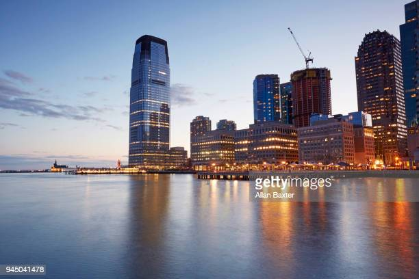 the jersey city waterfront with the '30 hudson street' tower at sunset - newark new jersey stock photos and pictures