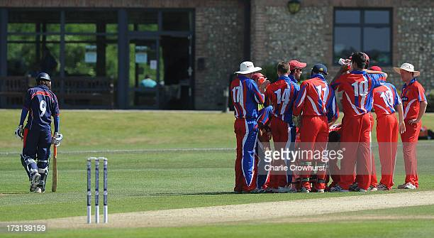 The Jersey team huddle after getting the wicket of Thomas Liddiard of France who walks back to the Pavilion during the European Division 1...