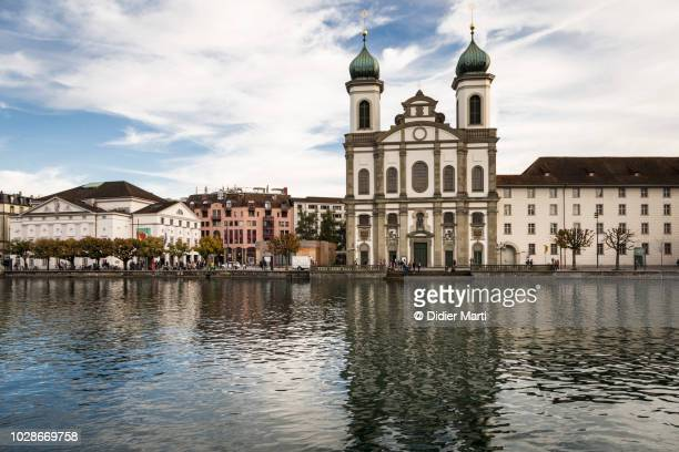the jesuit church and the famous chapel bridge in lucern - jesuit stock photos and pictures