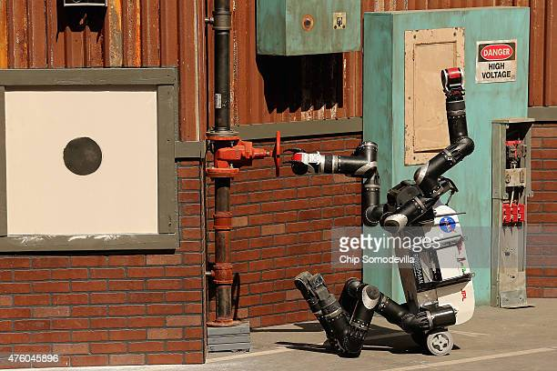 The Jet Propulsion Labs' Team RoboSimian 275pound robot uses one of its four limbs to turn a valve during the Defense Advanced Research Projects...