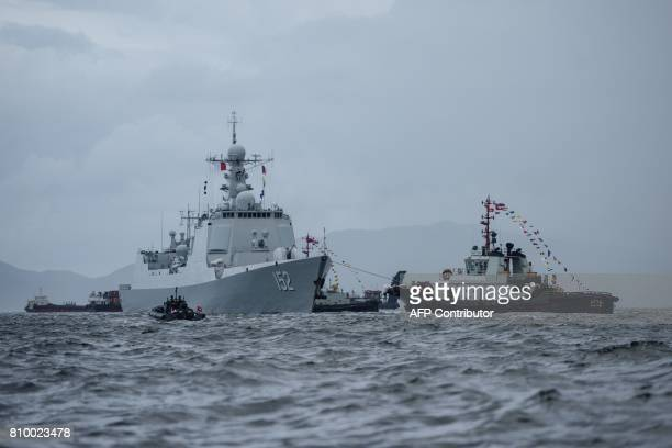 The Jinan a destroyer of China's People's Liberation Army Navy provides an escort ahead of the Liaoning aircraft carrier into the Lamma Channel as it...
