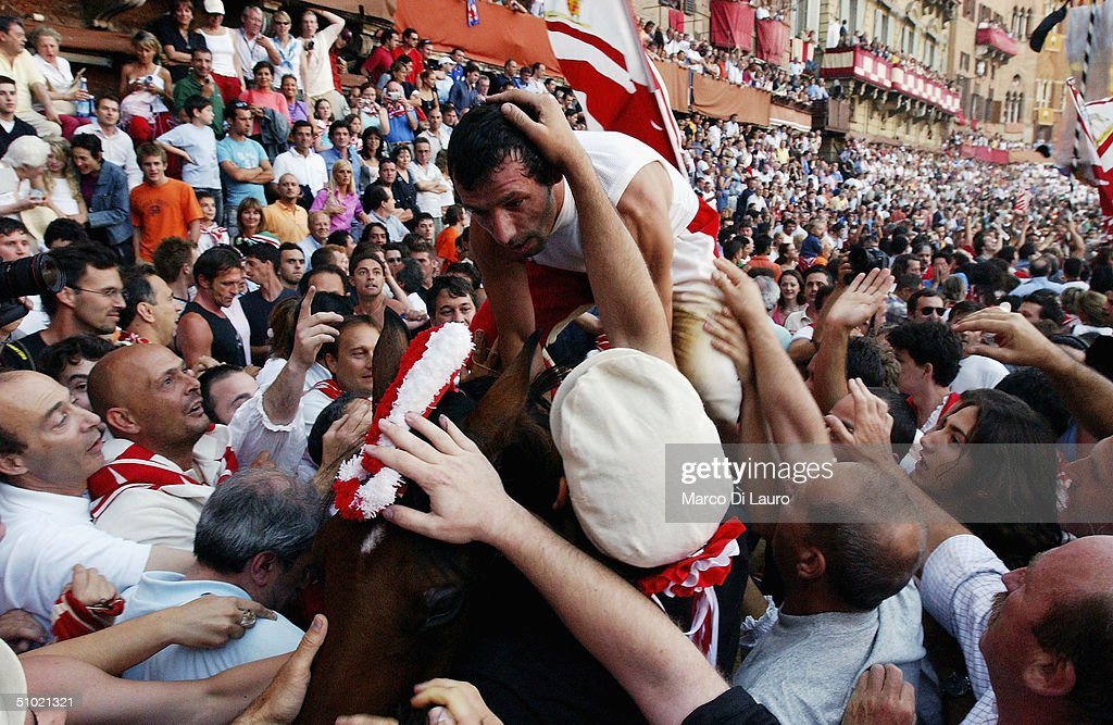 The jockey Alberto Ricceri belonging to the Giraffa (Giraffe), one of the seventeen Contrade or neighborooud, celebrates with his contradaioli in Piazza del Campo after winning the Palio horse race with his horse, Donosu Tou, on July 2, 2004 in Siena, Italy. The city's 17 separate Contrade or neighbourhoods vie to compete in the prestigious Palio race, which takes place at the end of a week of festivities which encourage huge support and fierce competition between the participants.