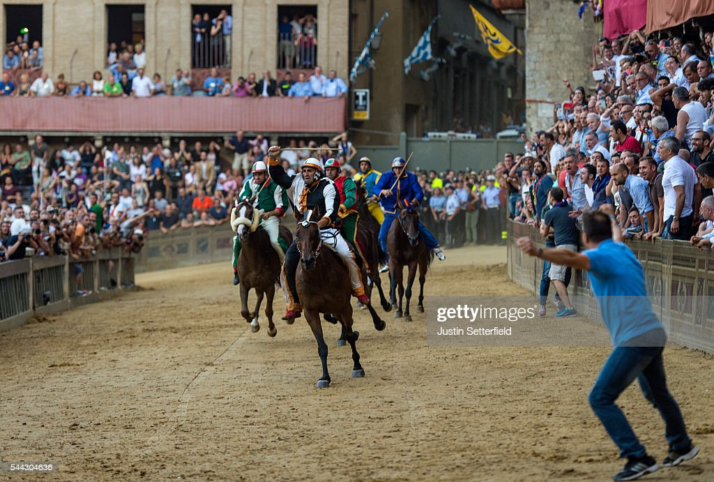 The jockey, Jonatan Bartoletti aka 'Scompiglio' of the 'Contrada of Lupa' celebrates winning the historical Italian horse race of the Palio Di Siena on July 02, 2016 in Siena, Italy. The Palio di Siena, known locally simply as Il Palio, is a horse race that is held twice each year on 2 July and 16 August, in Siena, Italy. Ten horses representing ten of the seventeen districts 'Contradas' with jockeys 'Fantini' riding bareback compete during a three lap race around a makeshift course built in the 'Piazza del Campo' the city's central square to win the Palio banner. The Palio di Siena is more than a simple horse race. It is the culmination of ongoing rivalry and competition between the contrade. The lead-up and the day of the race are invested with passion and pride. The Palio held on 2 July is named Palio di Provenzano, in honour of the Madonna of Provenzano, a Marian devotion particular to Siena which developed around an icon from the Terzo Camollia. The race winner is awarded a banner of painted silk, or palio, which is hand-painted by a different artist for each race.
