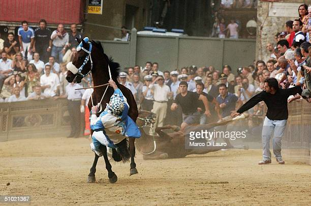 The jockey of the Onda one of seventeen contrade or neighboroouds holds onto his horse as he falls off in Piazza del Campo during the Palio horse...