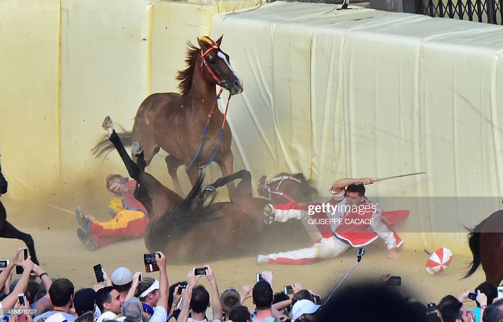 TOPSHOT - The jockeys of the 'Contrada of Giraffa ' (R) and 'Contrada of Chiocciola ' fall during the historical Italian horse race of the Palio of Siena on July 02, 2016 in Siena. / AFP / GIUSEPPE